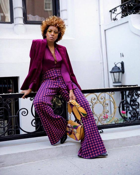 a super bright and chic fall work outfit with a silk purple blouse and a blazer, purple printed flare trousers and a tan bag