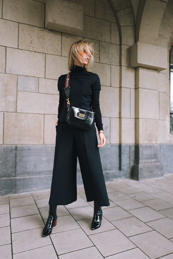 a total black look with a turtleneck, culottes, lacquer boots and a bag is totally wearable both at work and at a date