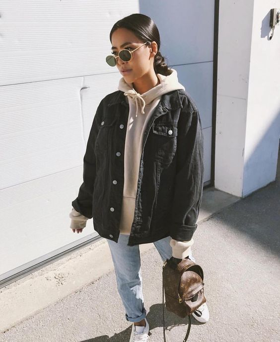 a neutral hoodie, an oversized black denim jacket, blue jeans, white sneakers and a brown backpack plus sunglasses