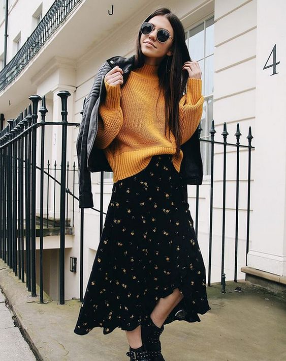 a pretty outfit with a black floral midi dress, a bold yellow sweater, black combat boots, a black leather moto jacket is amazing