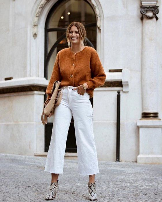 a rust-colored cardigan tucked into white cropped jeans, snakeskin printed boots, a tan bag for work on the fall