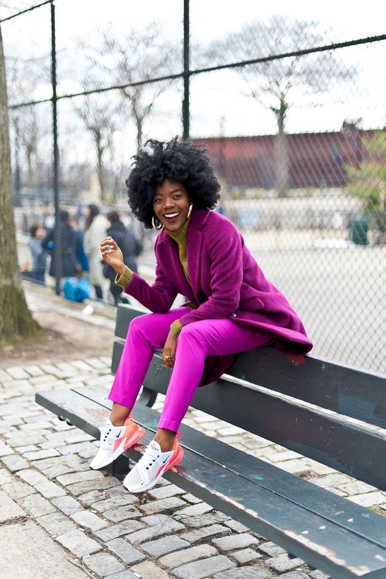 a stylish fall look with a tan turtleneck, fuchsia pants, a purple oversized blazer, white and pink trainers