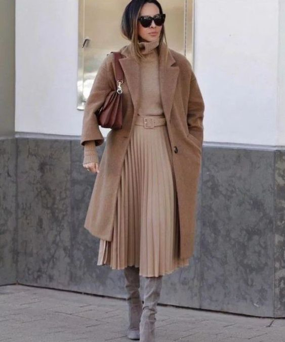 a pretty fall outfit with a tan turtleneck and a pleated midi skirt, a beige midi coat, grey boots and a brown bag
