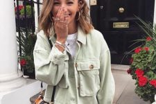 11 a pretty look with a white t-shirt, black jeans, a light green cropped denim jacket and a woven bag for warm fall days