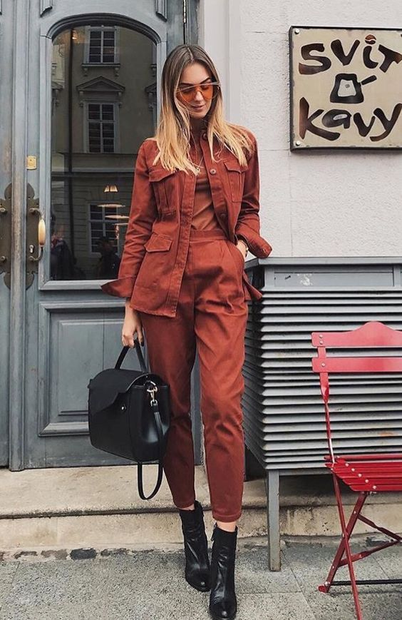 a rust-colored fall outfit with a turtleneck, high waisted trousers, a matching jacket, black boots and a bag is suitable for work