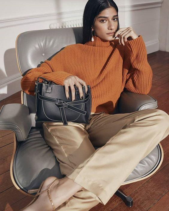 a simple and chic work outfit with a rust-colored chunky jumper, tan trousers, a catchy black bag for the fall