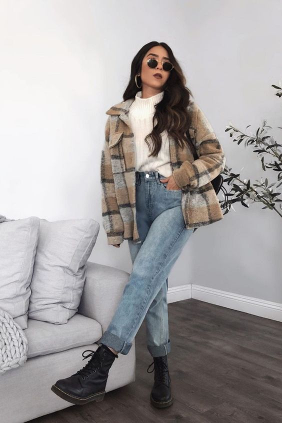 a simple and pretty college look with a white turtleneck sweater, blue jeans, a plaid shirt jacket, black boots and statement earrings