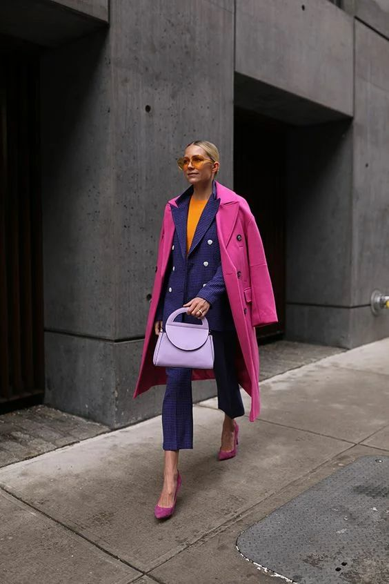 a colorful work look with an orange top, a violet printed pantsuit, a pink coat, pink shoes and a lilac bag