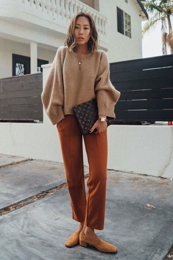 a tan oversized sweater, rust trousers, beige loafers and a brown bag for a cool fall work look