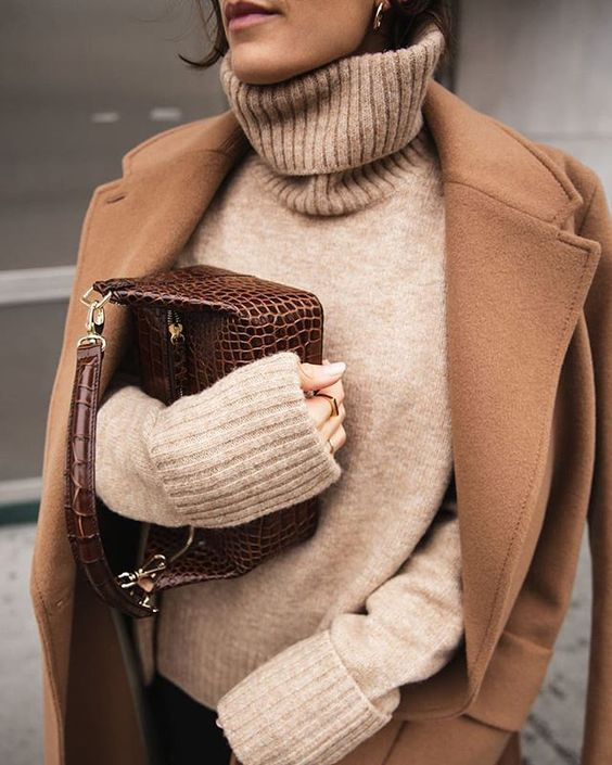 a tan turtleneck sweater, black jeans, a brown midi coat and a deep chocolate brown bag