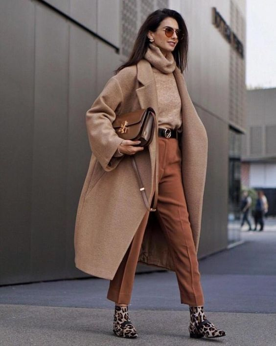 a tan turtleneck sweater, rust-colored trousers, a beige midi coat, a brown bag and leopard print boots