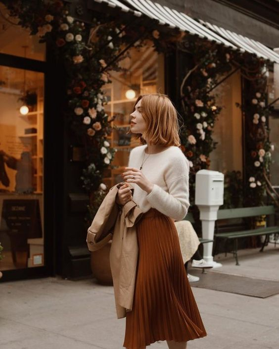 a white cashmere jumper, a rust-colored pleated midi skirt, a tan trench, a neutral bag for work in the fall