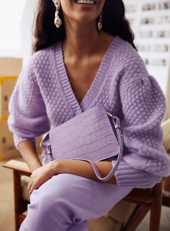 a dreamy lilac outfit with a V-neckline sweater, trousers and a clutch, all matching, and romantic earrings