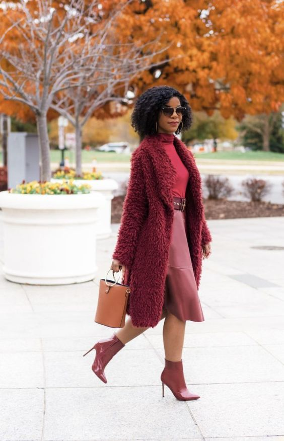 a monochromatic burgundy look with a turtleneck, a faux leather skirt, boots with heels and a tan bucket bag
