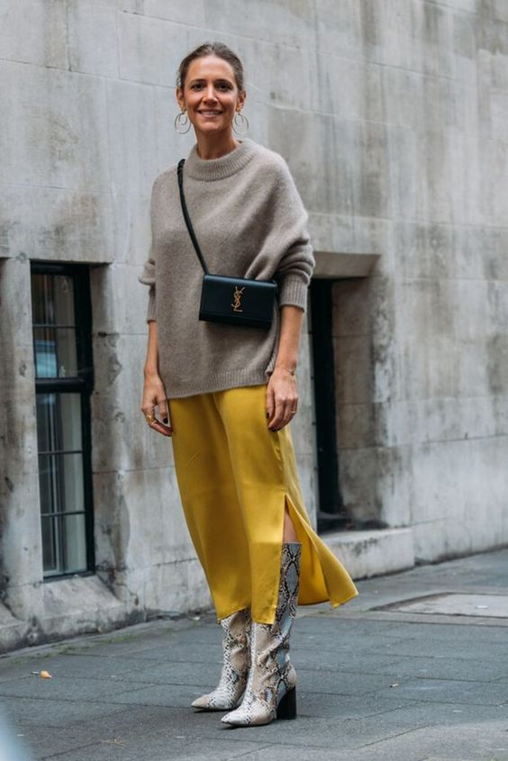 a stylish fall outfit with a mustard slip midi dress, a grey oversized sweater, snakeskin print boots, a black mini bag