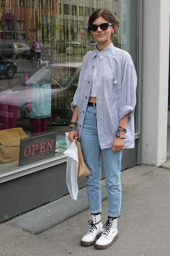 a white crop top, blue jeans, white boots, a blue oversized shirt and a black belt for the fall