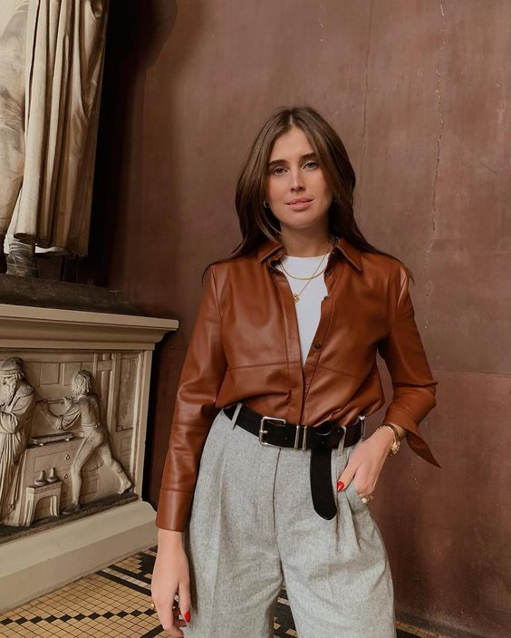 a white t-shirt, grey high waisted trousers, a rust-colored leather shirt, layered necklaces and a black belt