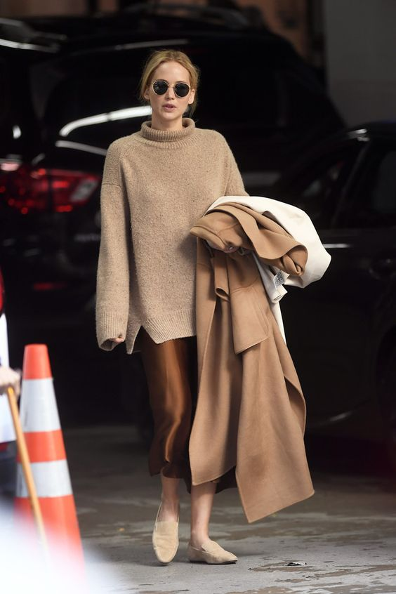 a beautiful monochromatic look with a chocolate brown slip midi dress, a tan oversized sweater, nude loafers and a beige coat by Jennifer Lawrence