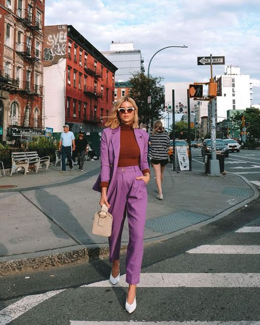 a fall work look with a purple pantsuit, a rust turtleneck, white heels and a tan bucket bag