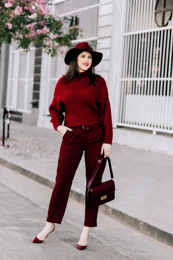a monochromatic burgundy outfit with trousers, a sweater, high heels, a bag, a hat and earrings plus a matching lipstick