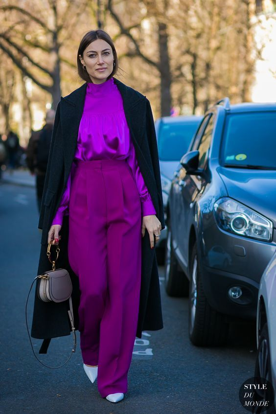 a refined fall work outfit with a silk purple blouse and high waisted palazzo trousers, white shoes, a black trench and a neutral bag
