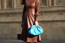 18 a bold and chic fall outfit with a leather A-line midi dress, matching brown boots and a bold blue clutch for an accent