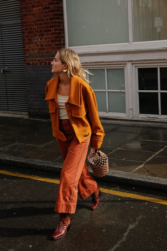 a bright fall outfit with a white top, a rust-colored shirt jacket, burnt orange jeans, burgundy boots, a bucket bag and statement earrings