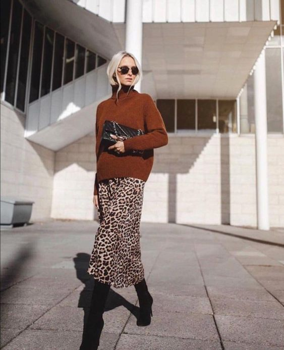 a leopard print midi skirt, a rust colored sweater, black boots and a black clutch for a super elegant fall look