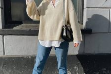 18 a white shirt, a creamy oversized pullover, blue jeans, black sneakers and a black mini bag for a comfy college look
