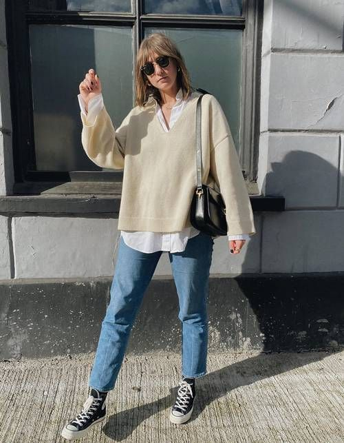 a white shirt, a creamy oversized pullover, blue jeans, black sneakers and a black mini bag for a comfy college look