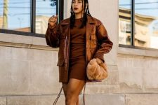 19 a bold monochromatic brown look with a brown mini dress, a brown oversized leather jacket, creamy boots and a rust-colored faux fur bag