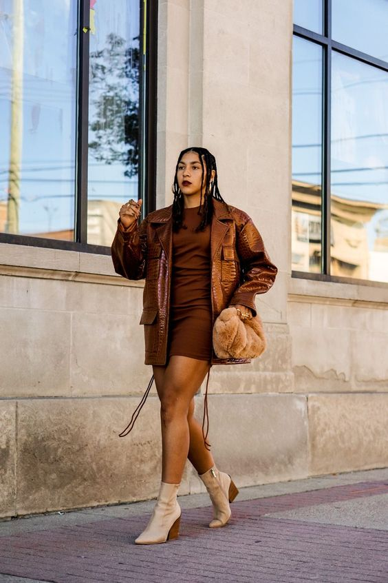 a bold monochromatic brown look with a brown mini dress, a brown oversized leather jacket, creamy boots and a rust-colored faux fur bag