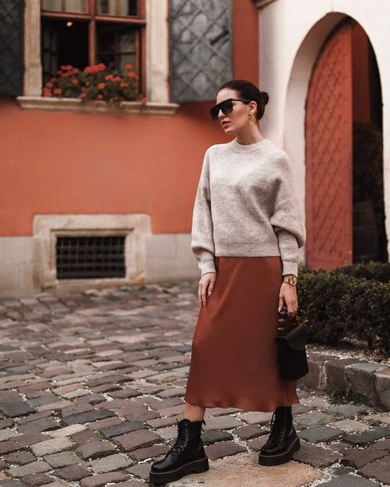 a neutral jumper, a rust-colored slip midi skirt, black boots, a black bag and statement earrings for a cool and bold look