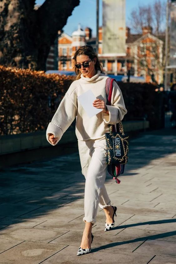 a neutral look with an oversized sweater, white jeans spruced up with black and white polka dot shoes and a catchy bag