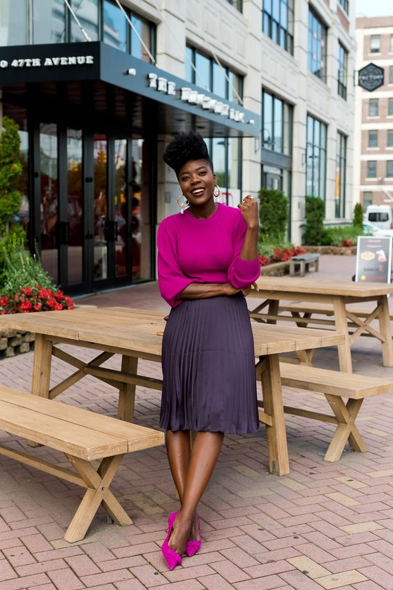 a pretty fall work outfit with a purple top, a lavender grey pleated midi, fuchsia shoes and statement earrings