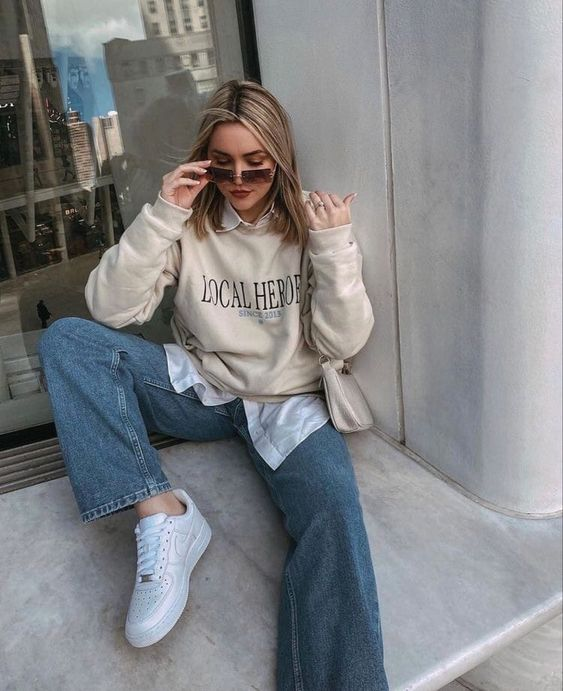 a white shirt, a creamy sweatshirt, blue jeans, white sneakers and a creamy bag for a lovely fall look