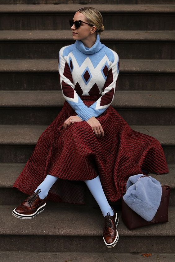 a bold look with a blue, white and burgundy geo print sweater, a burgundy A-line skirt, burgundy shoes, blue stockings and a jacket