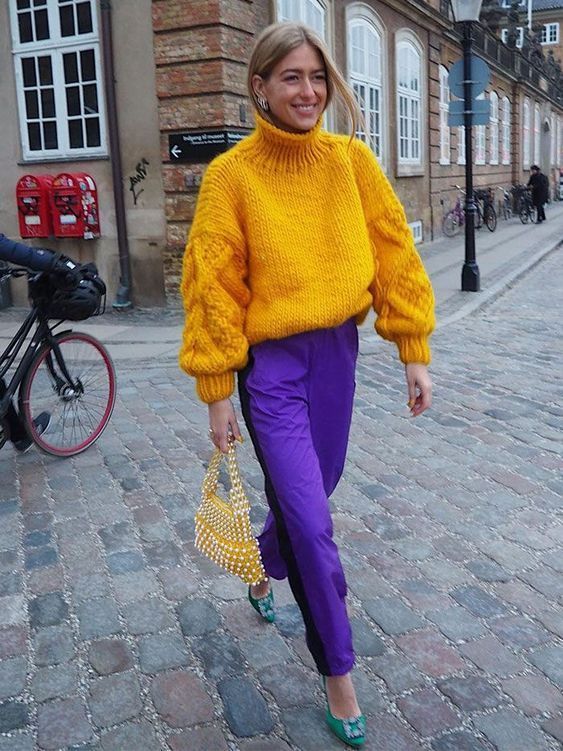 a colorful fall outfit with an oversized chunky marigold sweater, purple trousers, emerald heels and an embellished bag