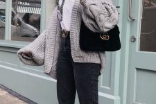 20 a white shirt, black jeans, a logo belt, white sneakers, an oversized chunky grey cardigan and a black bag
