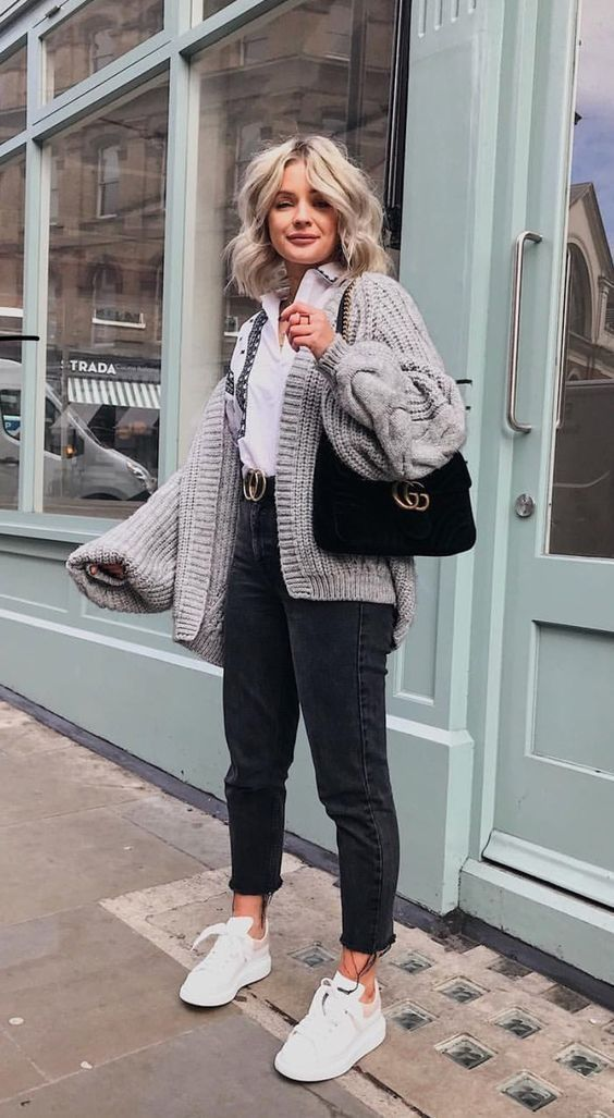 a white shirt, black jeans, a logo belt, white sneakers, an oversized chunky grey cardigan and a black bag