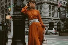21 a rust-colored midi dress, a snakeskin print belt, black lacquer boots, a white bag and statement earrings for a wow effect