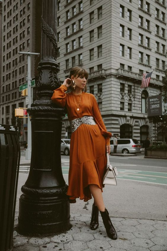 a rust-colored midi dress, a snakeskin print belt, black lacquer boots, a white bag and statement earrings for a wow effect