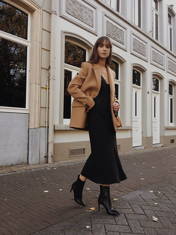 an elegant fall outfit for work with a black slip midi dress, a tan oversized blazer, black boots and a tan bag
