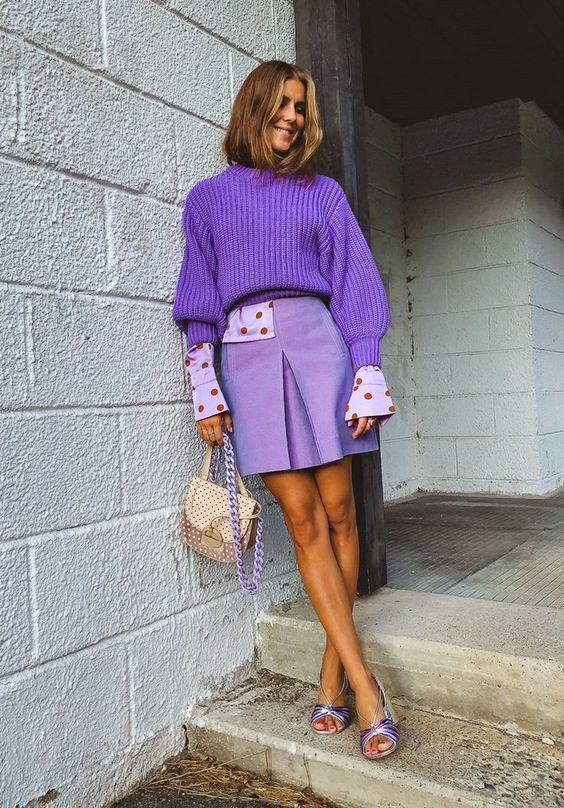 a dreamy lavender outfit with a lilac and red polka dot shirt, a purple chunky sweater, a lilac leather skirt, lilac shoes and a tan bag