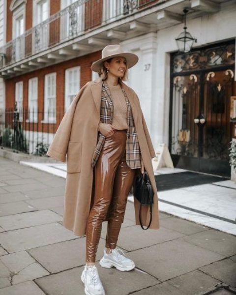 a monochromatic fall outfit with a tan jumper, a plaid blazer, brown vinyl pants, white trainers, a beige midi coat and a creamy hat