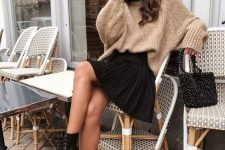 22 a tan oversized sweater, a black pleated mini skirt, black boots and an embellished black bag for a lovely and girlish look