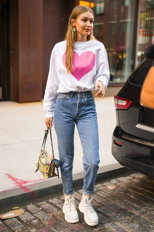 a white sweatshirt with a heart print, blue jeans, white boots, bold earrings and a bold printed bag