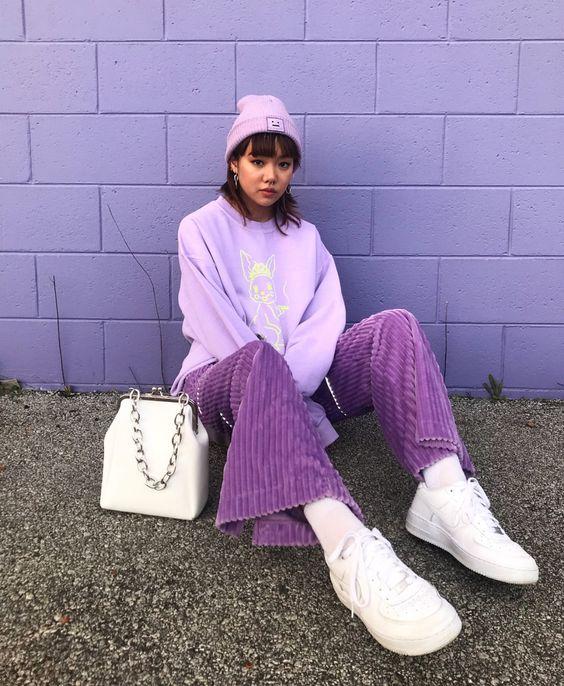 a lilac printed sweatshirt, a lilac beanie, purple corduroy pants, white snekaers and a white bag