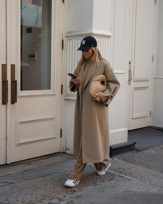 a monochromatic tan and beige look with a sweater, trousers, a midi coat, a tan leather bag, white sneakers and a cap