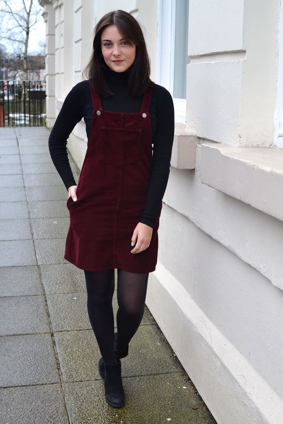 a pretty retro-inspired fall look with a black turtleneck, a burgundy overall, black tights and boots